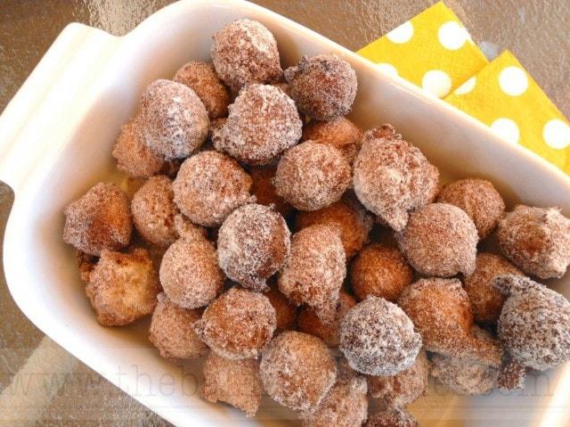 A pan of sugar coated, deep fried, gluten free doughnut holes