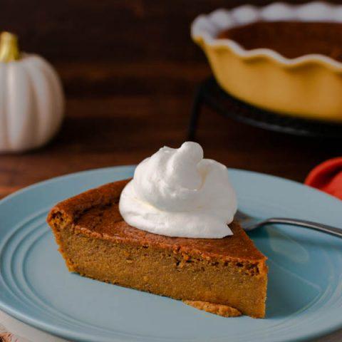 A slice of crustless pumpkin pie on a blue plate