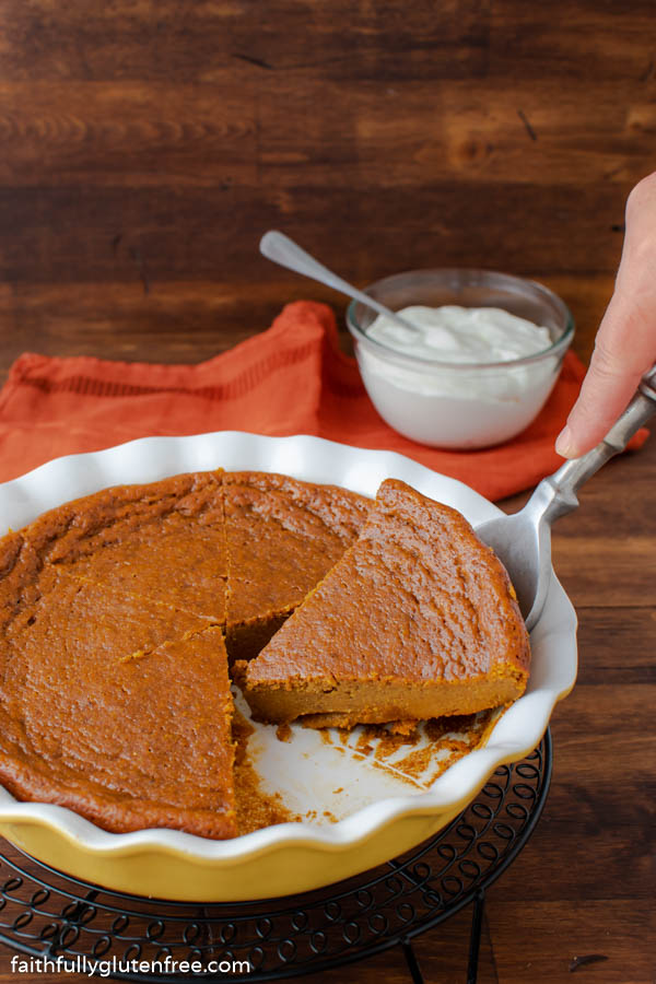 A slicer of crustless pumpkin pie being lifted out of the pie pan