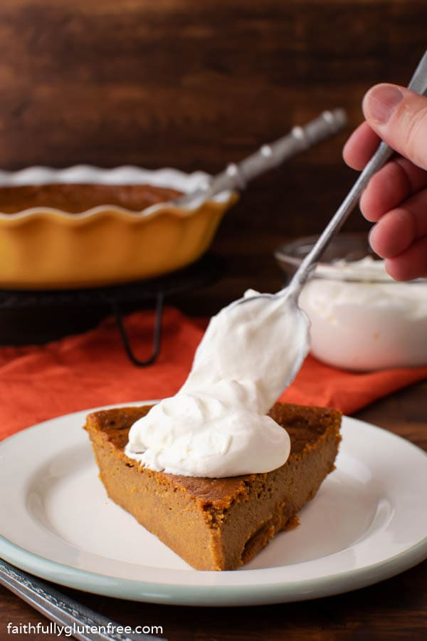 A slice of pumpkin pie getting a dollop of whipped cream