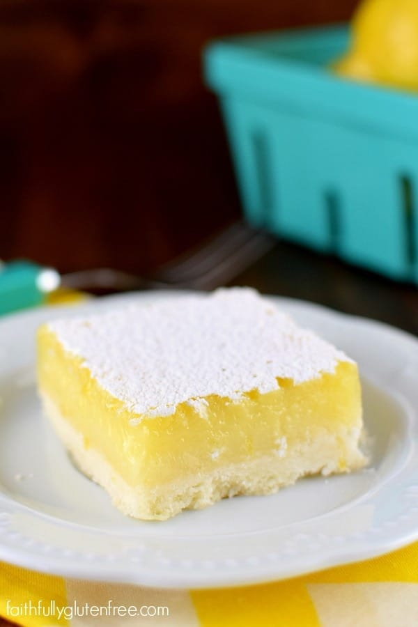 A plate with a big, beautiful piece of gluten free Lemon Bars with a thick layer of lemon curd and sprinkled with powdered sugar on top.