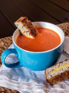 A bowl full of gluten free and dairy free tomato soup served with grilled cheese.