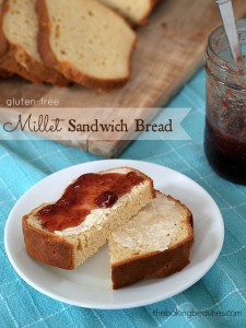 Slices of gluten free Millet Sandwich Bread, smothered with homemade strawberry jam, on a white plate.