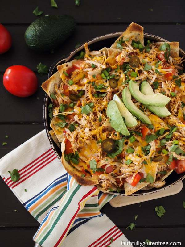 A skillet full of chicken nachos, topped with salsa, cheese, peppers, and sliced avocado.