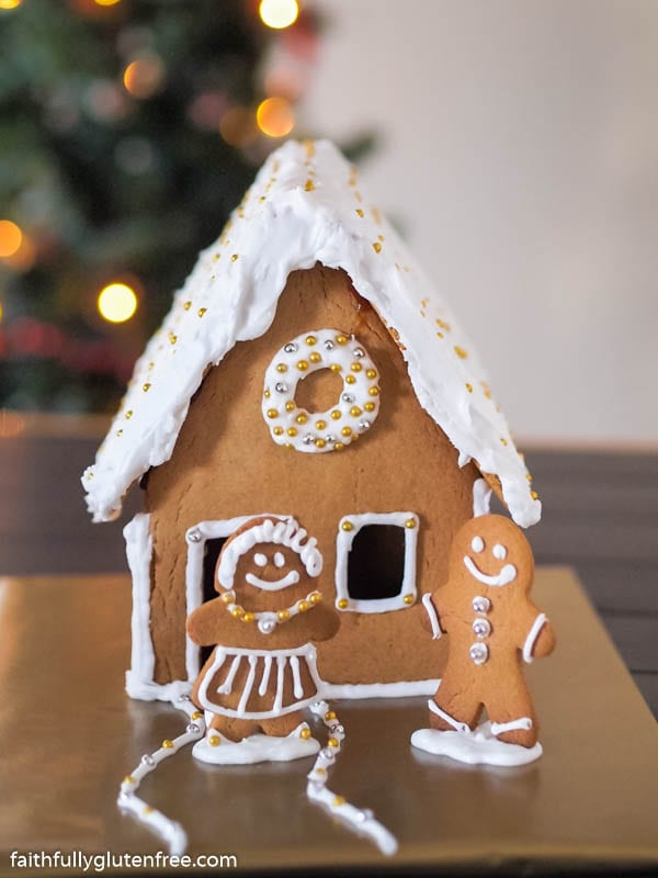 Gingerbread house with a man and woman standing outside
