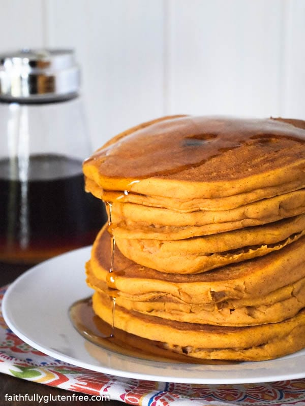 Tall stack of pumpkin pancakes dripping with maple syrup