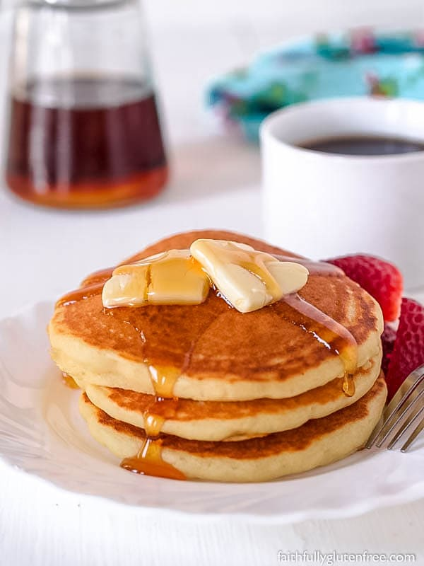 Small stack of pancakes with butter and syrup