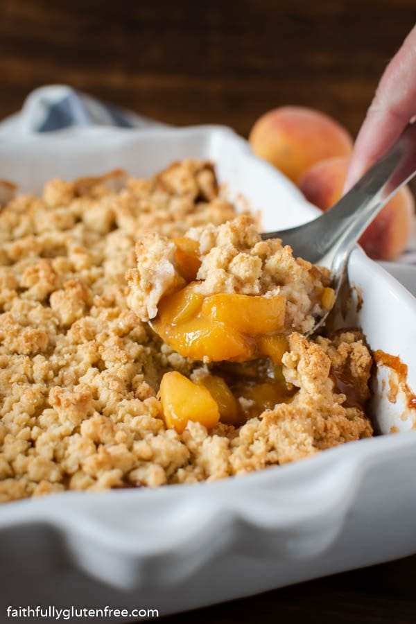 Peach Cobbler being spooned from a baking pan