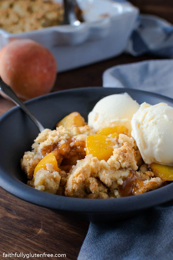 a bowl of peach cobbler with ice cream