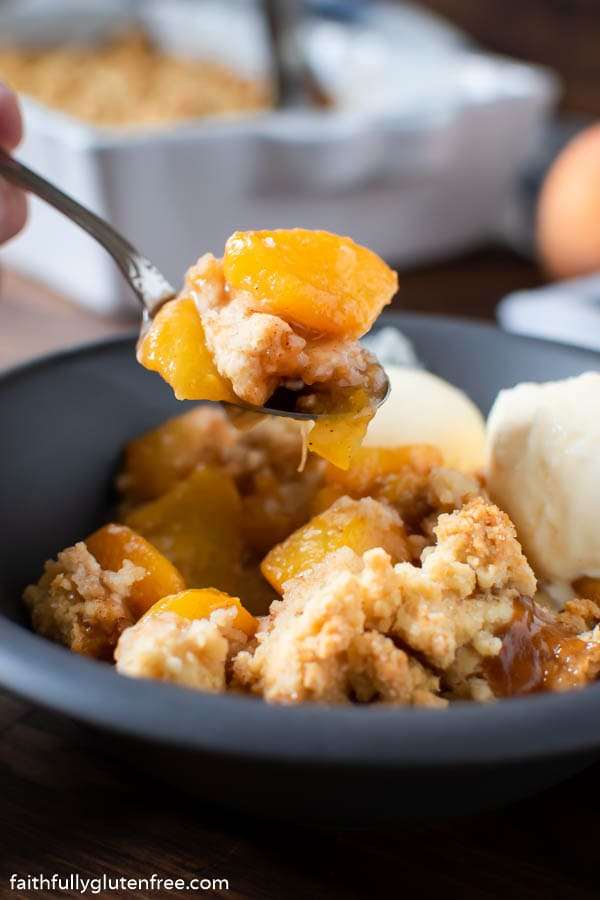 A spoon with homemade peach cobbler