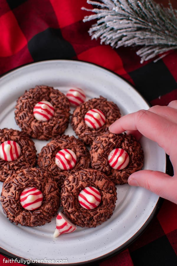 Plate of chocolate cookies with candy cane kisses on them
