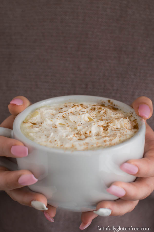 Hands holding a large mug topped with whipped cream
