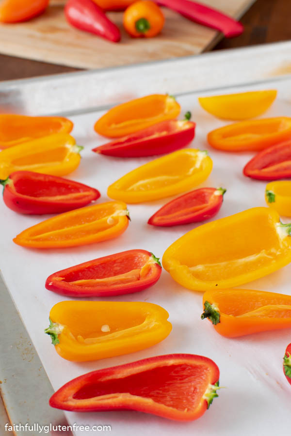 Halved mini sweet peppers on a baking pan