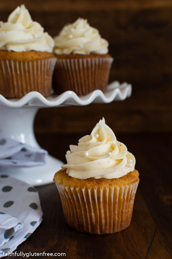 Cupcakes topped with buttercream on a dark background
