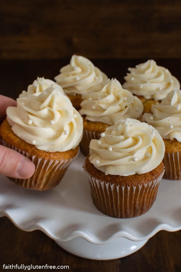 A hand reaching for a cupcake