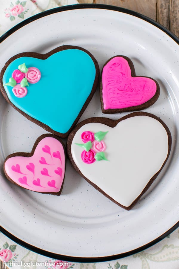 a plate of heart cookies with white, blue and pink icing