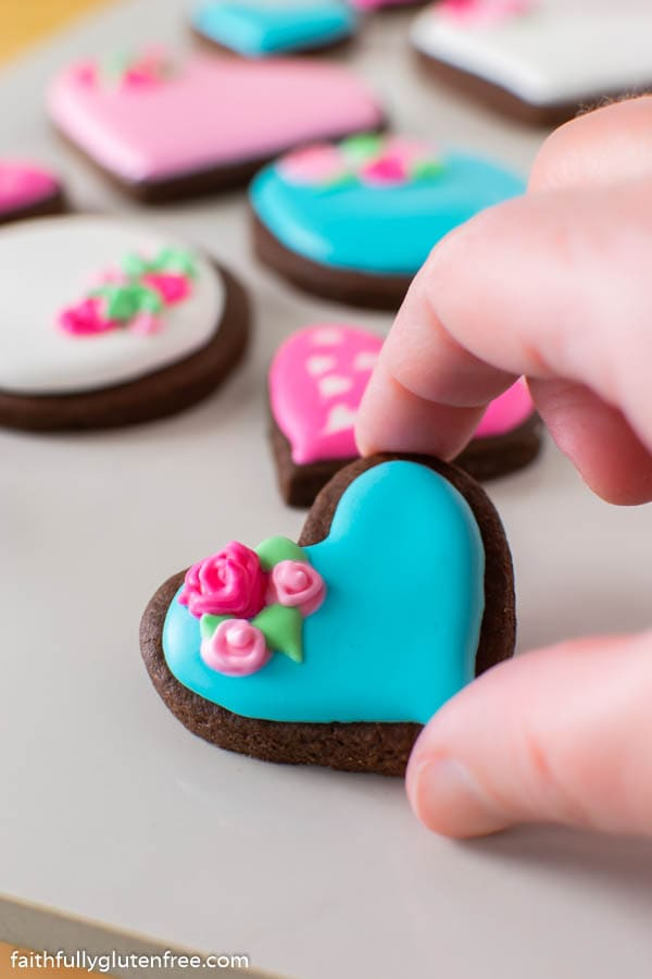 a hand picking up a small valentine's cookie