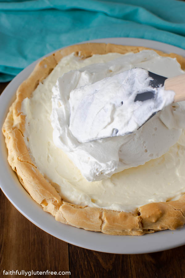 Spreading whipped cream on top of a pie