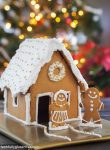 A gingerbread house decorated with silver and gold